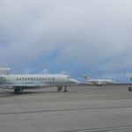 Photograph of two private aircraft on the apron and a chartered Airlink E190 landing in the distance