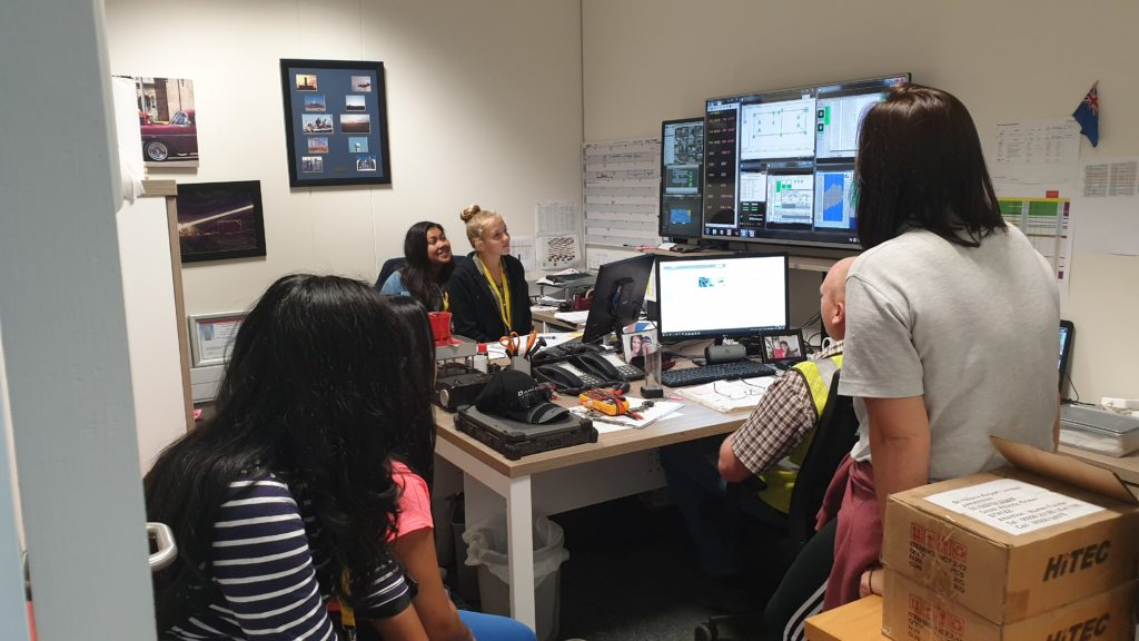 Photo of BASH young people in the Communications and Navigation office viewing monitoring systems for airport systems