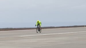 Photo of Dr Sergio cycling on the runway at St Helena Airport at the SHAPE Superhero Fun Day on 14 November 2020